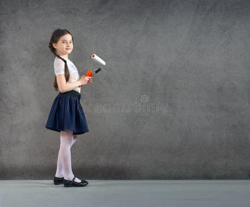 La niña joven sonriente alegre el niño dibuja en los colores de la pared del fondo reparar creativos fotografía de archivo libre de regalías