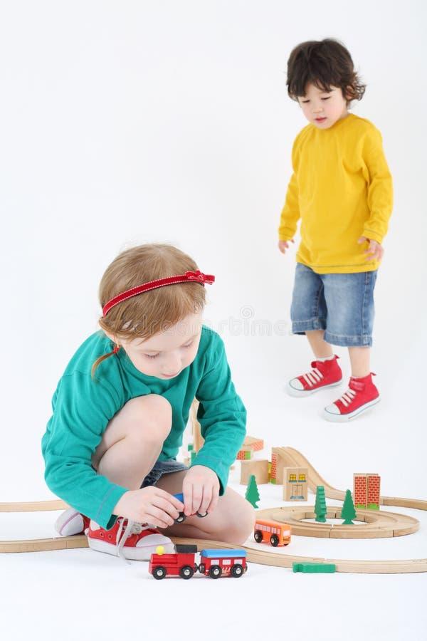 La niña juega con el tren y el ferrocarril y el muchacho de madera mira imágenes de archivo libres de regalías