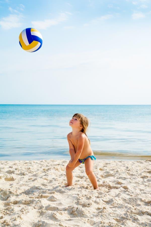 La niña juega a voleibol en una playa del mar fotos de archivo libres de regalías