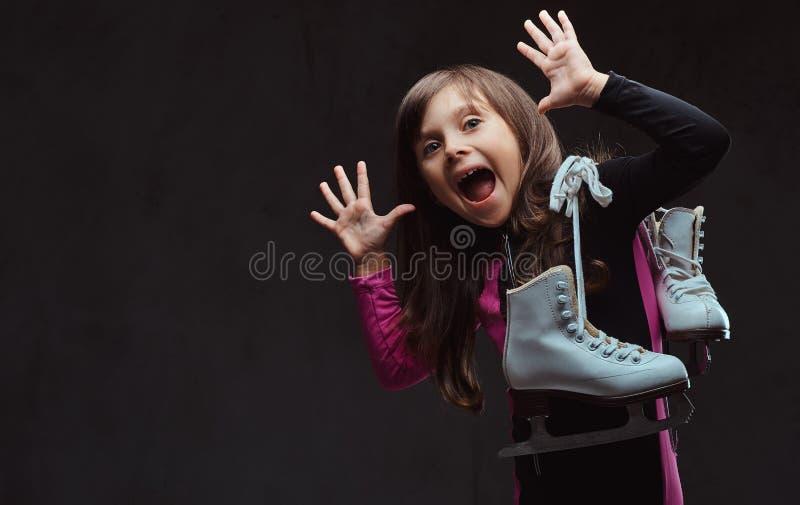 La niña juguetona con una cara divertida vestida en ropa de deportes sostiene patines de hielo Aislado en un fondo texturizado os imagenes de archivo
