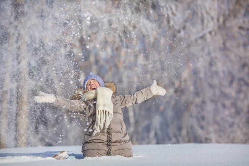 La niña lanza para arriba nieve y ríe en invierno imágenes de archivo libres de regalías