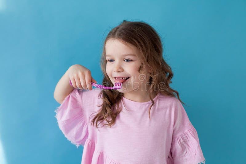 La niña limpia la abolladura del cepillo de dientes de los dientes agradable foto de archivo