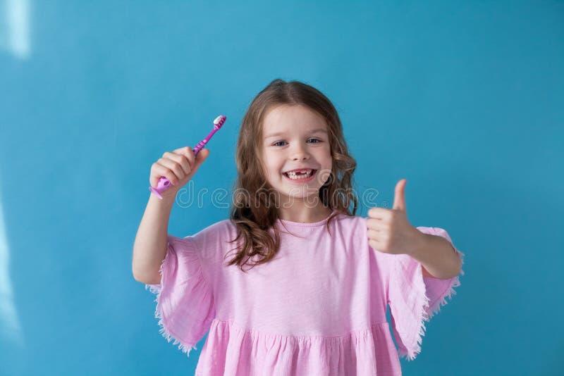 La niña limpia la abolladura del cepillo de dientes de los dientes agradable fotos de archivo