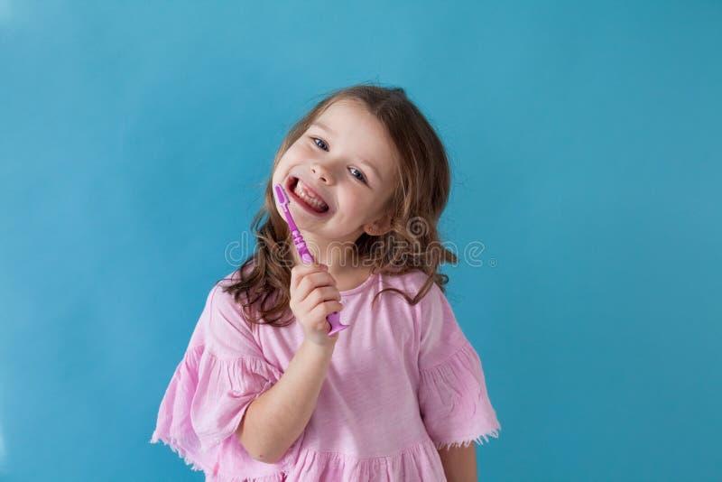 La niña limpia la atención sanitaria de la odontología de los dientes agradable fotos de archivo