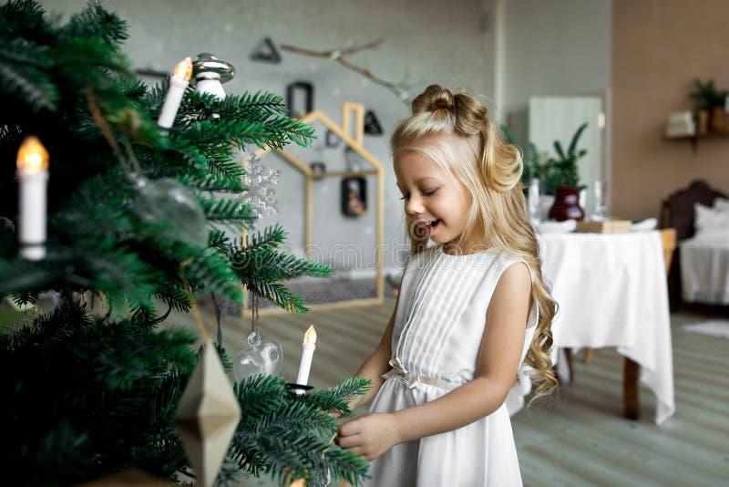 La niña linda adorna un árbol de navidad Feliz Navidad y buenas fiestas imagen de archivo