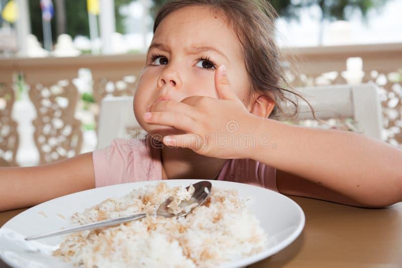 La niña linda come el arroz en un café del verano fotos de archivo libres de regalías