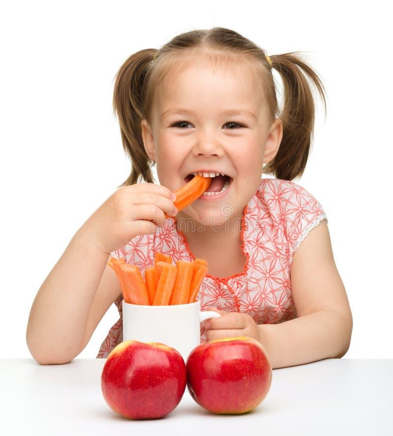 La niña linda come la zanahoria y manzanas fotos de archivo