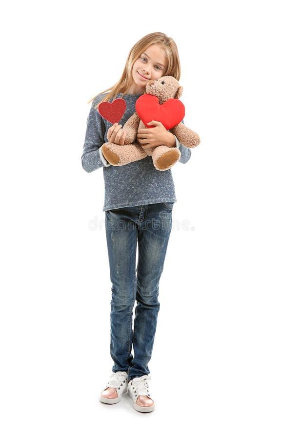 La niña linda con el corazón rojo y el peluche refieren el fondo blanco fotos de archivo