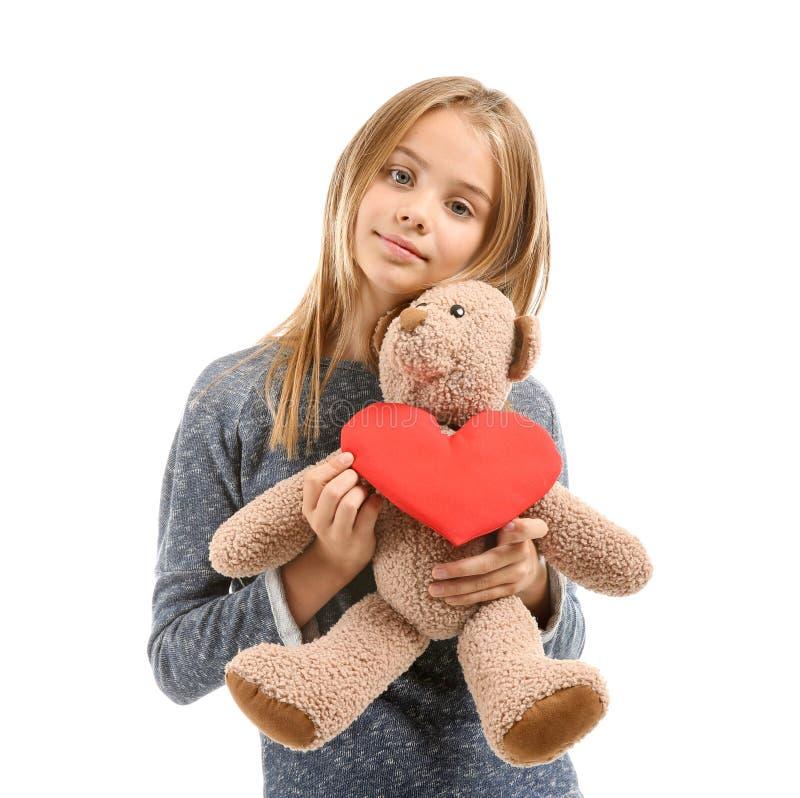 La niña linda con el corazón rojo y el peluche refieren el fondo blanco fotografía de archivo