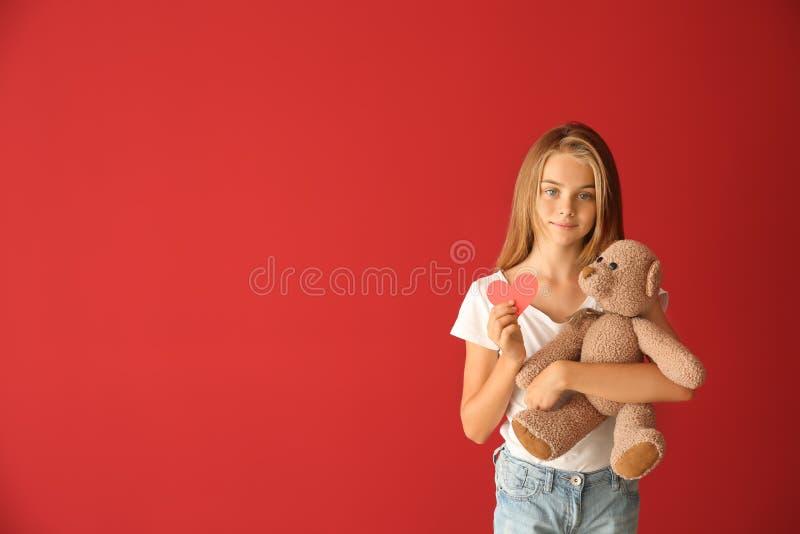 La niña linda con el corazón rojo y el peluche refieren el fondo del color imagen de archivo