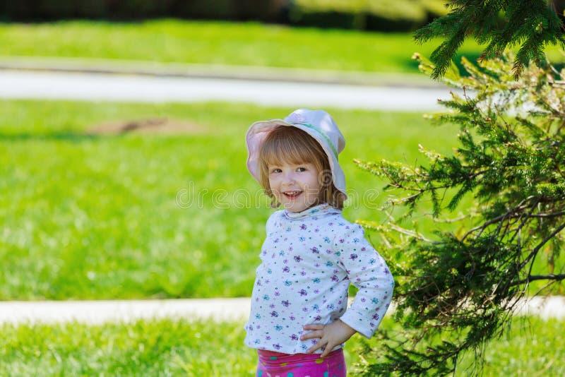 La niña linda consigue el diente de león y la sonrisa, familia feliz que tiene jugar al aire libre, naturaleza de la diversión de foto de archivo