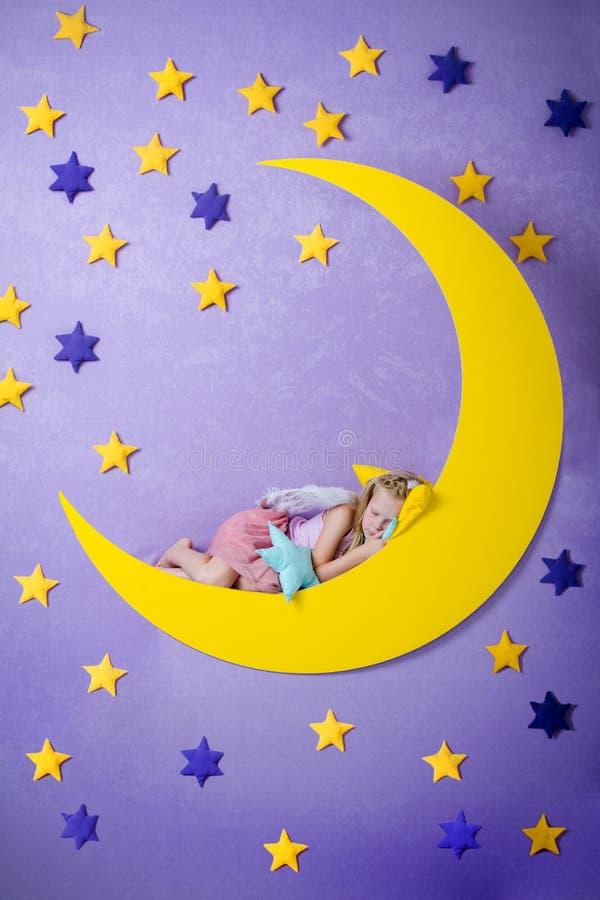 La niña linda duerme en una luna grande imagen de archivo