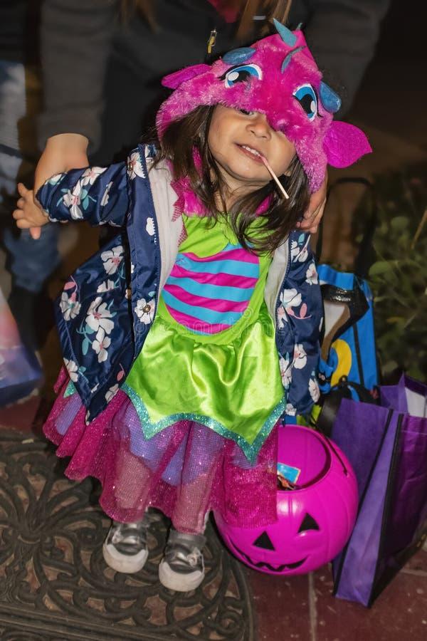 La niña linda en el traje colorido de Halloween y el lechón en sus esperas de la boca en el pórtico para el truco r tratan el car imagen de archivo