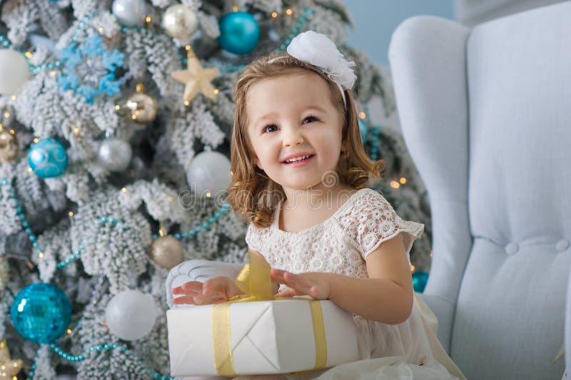 La niña linda en el vestido del bklom que se sienta en una silla y abre la caja con el presente para el azul del árbol de navidad fotos de archivo libres de regalías