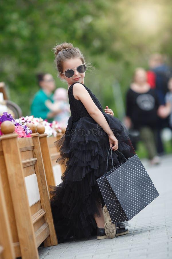 La niña linda en gafas de sol y un vestido de noche hermoso va a hacer compras en un boutique prestigioso imágenes de archivo libres de regalías