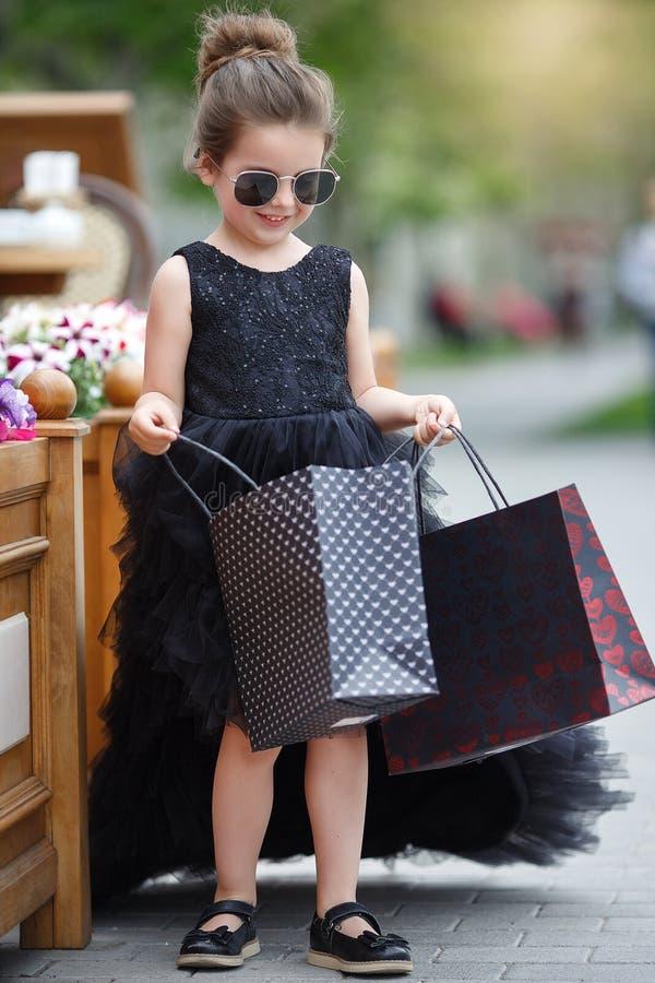 La niña linda en gafas de sol y un vestido de noche hermoso va a hacer compras en un boutique prestigioso imagen de archivo