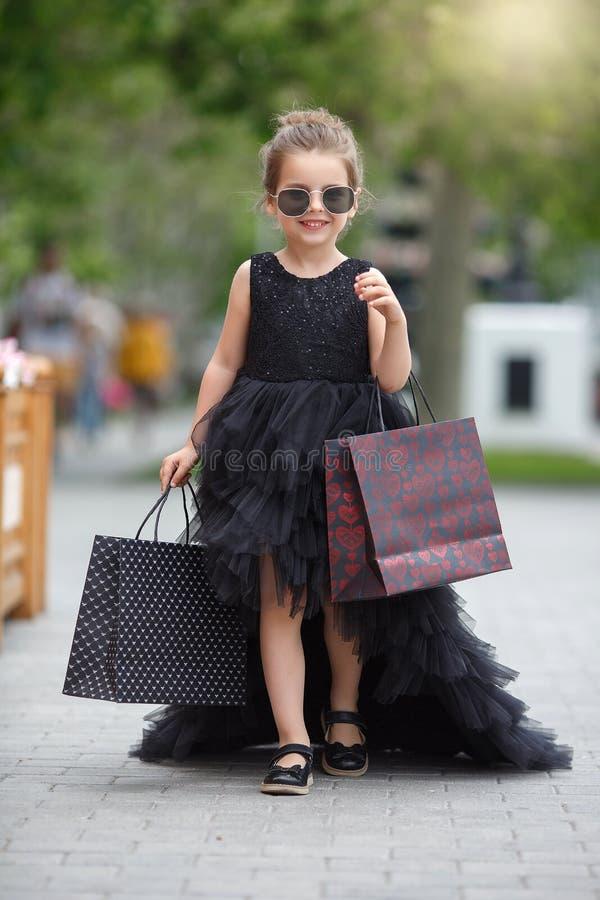 La niña linda en gafas de sol y un vestido de noche hermoso va a hacer compras en un boutique prestigioso fotografía de archivo