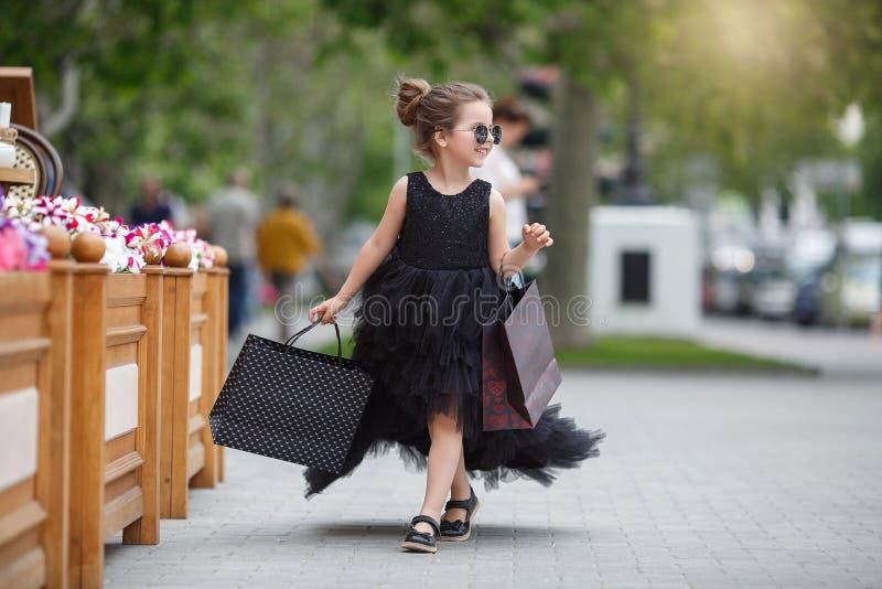 La niña linda en gafas de sol y un vestido de noche hermoso va a hacer compras en un boutique prestigioso imagenes de archivo