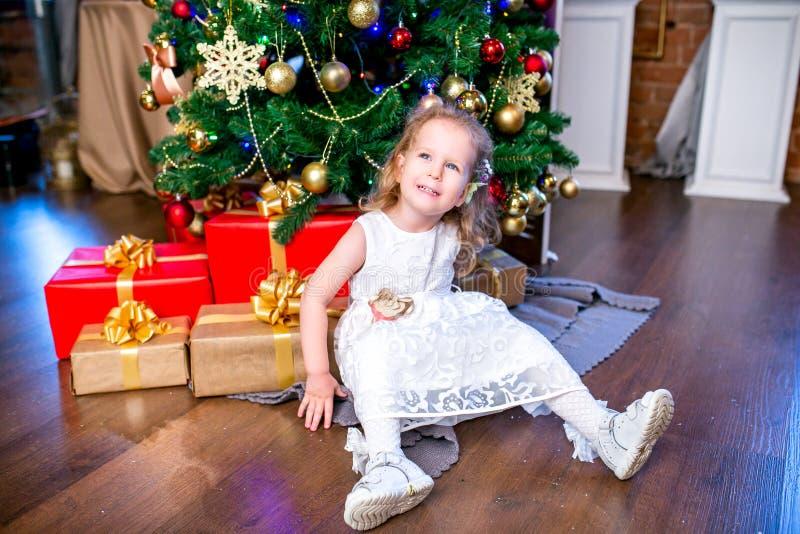 La niña linda en un vestido blanco se sienta cerca de un árbol de navidad con los regalos y mira para arriba imagen de archivo libre de regalías