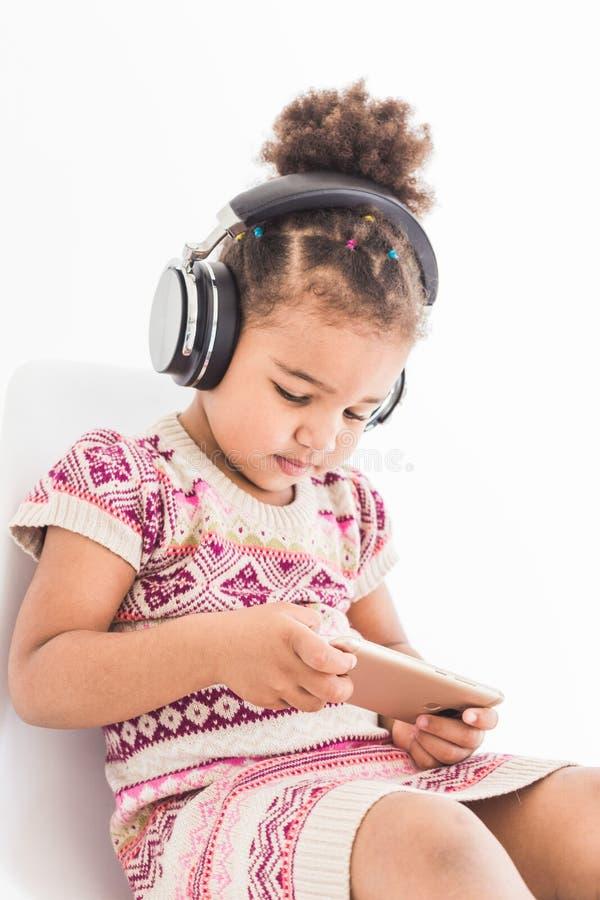 La niña linda en un vestido multicolor, escucha la música con los auriculares y utiliza un smartphone en un fondo blanco imagen de archivo