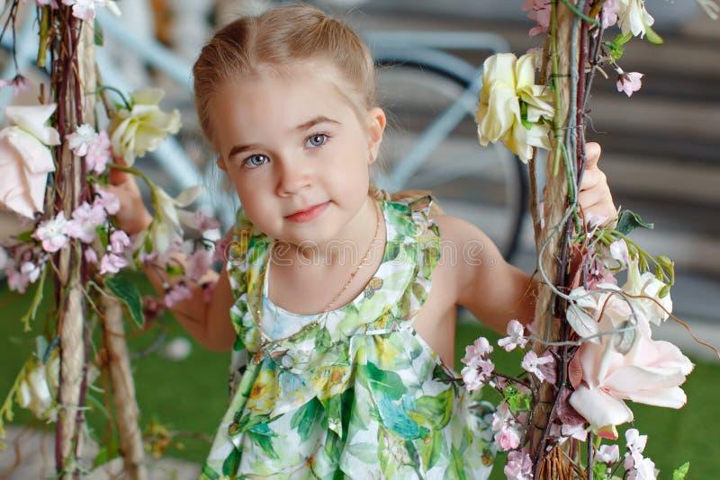 La niña linda en un vestido verde que se sentaba en oscilaciones adornó los wi foto de archivo