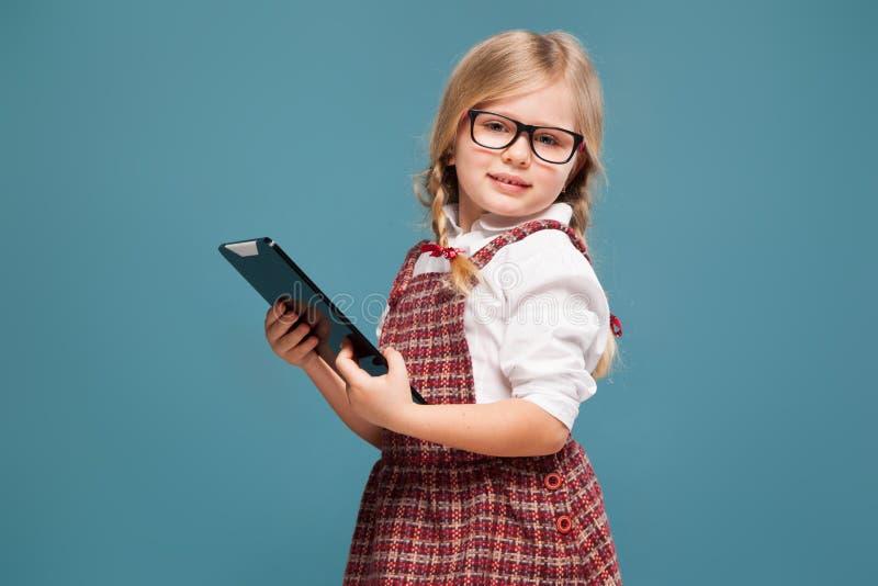 La niña linda en vestido rojo, la camisa blanca y vidrios sostiene la tableta vacía imagenes de archivo