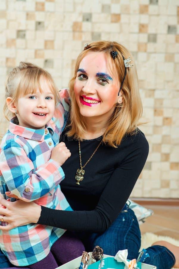 La niña linda es el hacer divertido compone a su madre foto de archivo libre de regalías