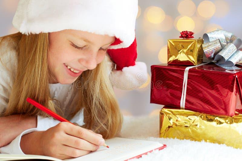 La niña linda escribe la letra a Santa Claus imagen de archivo