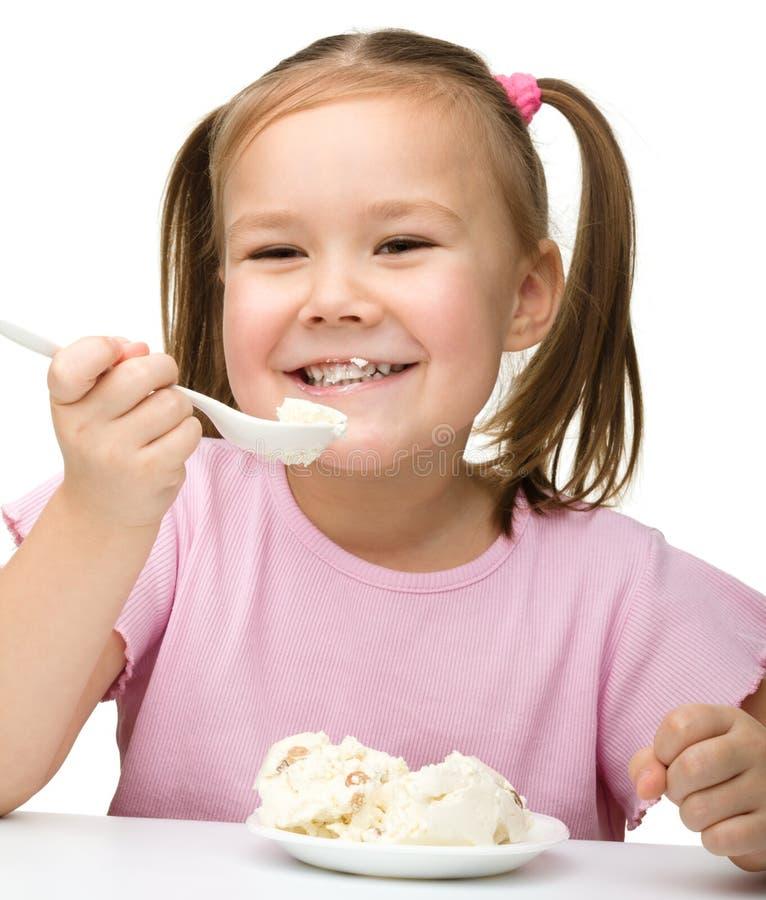 La niña linda está comiendo el requesón fotografía de archivo