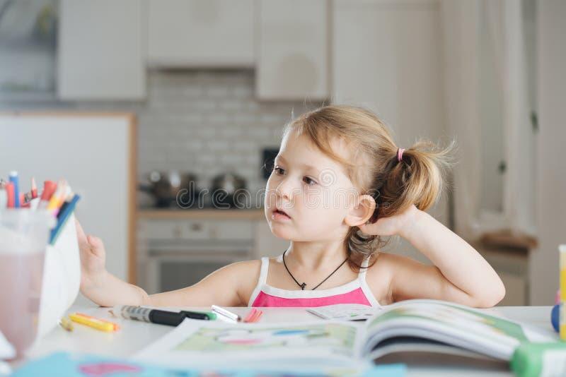 La niña linda está dibujando con el rotulador en casa fotos de archivo