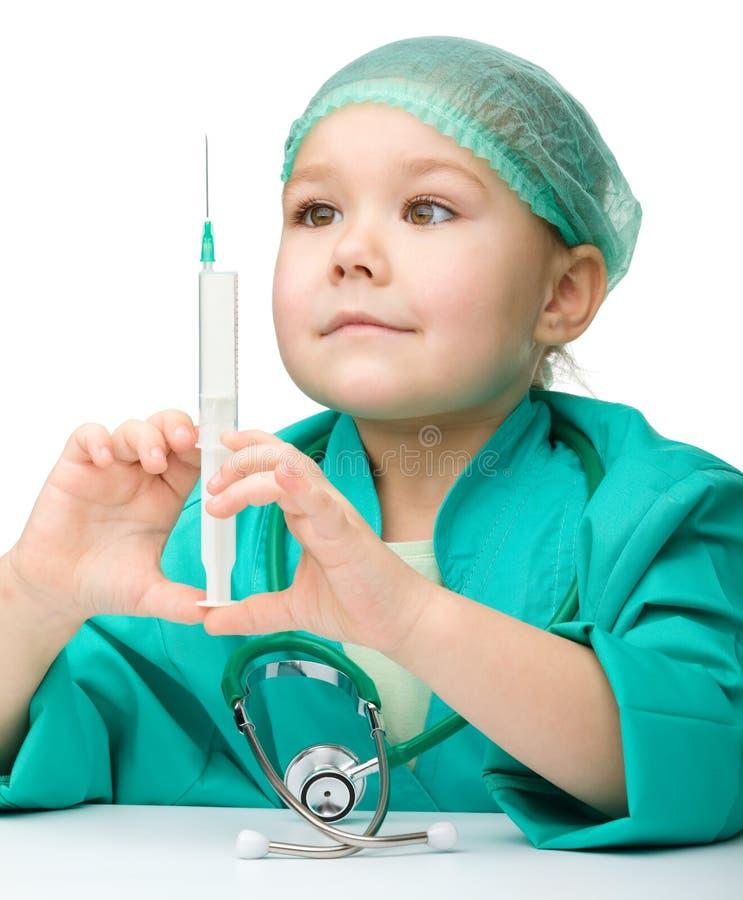 La niña linda está jugando al doctor con la jeringuilla foto de archivo