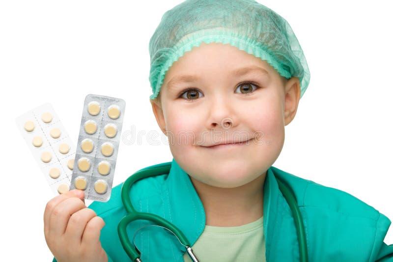La niña linda está jugando al doctor con las píldoras imágenes de archivo libres de regalías
