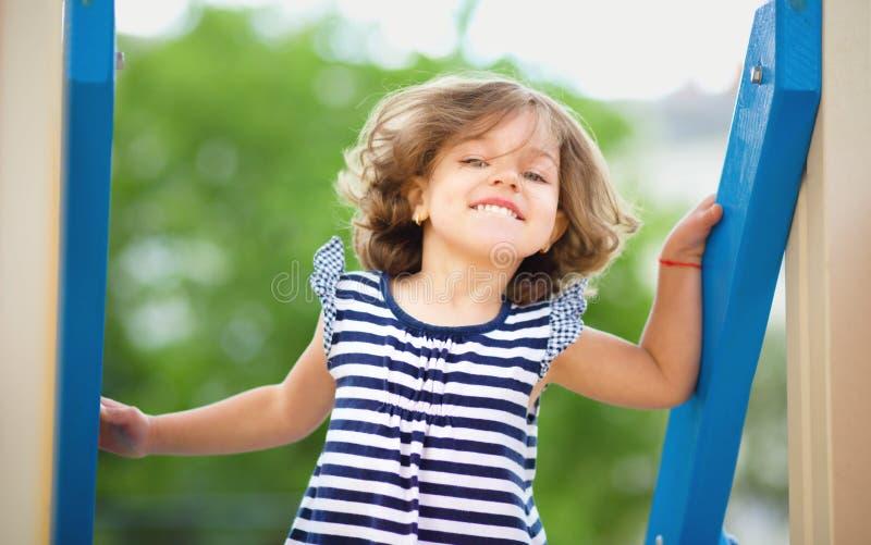 La niña linda está jugando en patio fotografía de archivo