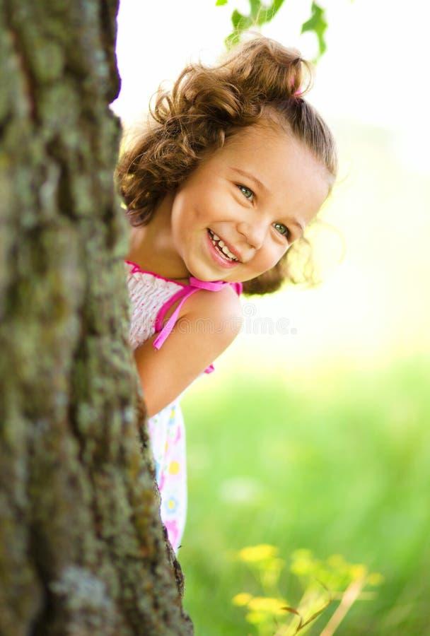 La niña linda está jugando escondite imagen de archivo