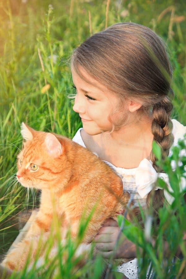 La niña linda está sosteniendo un gato rojo que se sienta en la hierba fotos de archivo