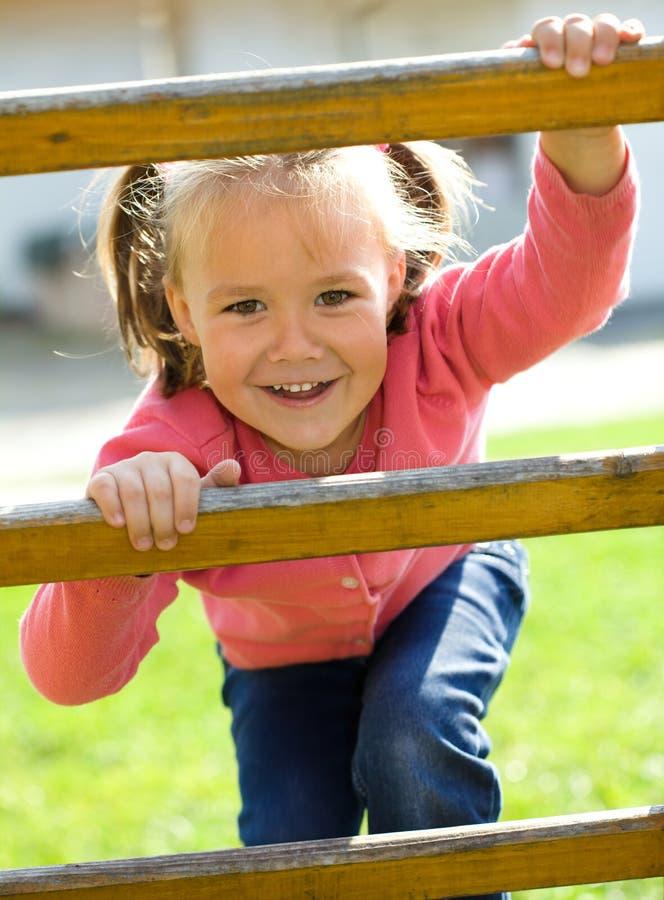 La niña linda está subiendo para arriba en escala fotos de archivo libres de regalías