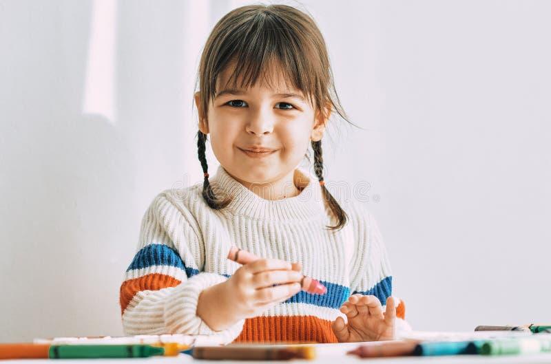 La niña linda feliz pinta con los lápices del aceite, sentándose en el escritorio blanco en casa El niño preescolar sonriente bon fotos de archivo libres de regalías
