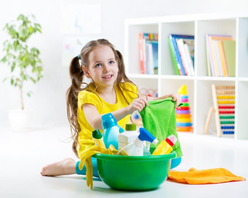 La niña linda limpia un piso imagenes de archivo