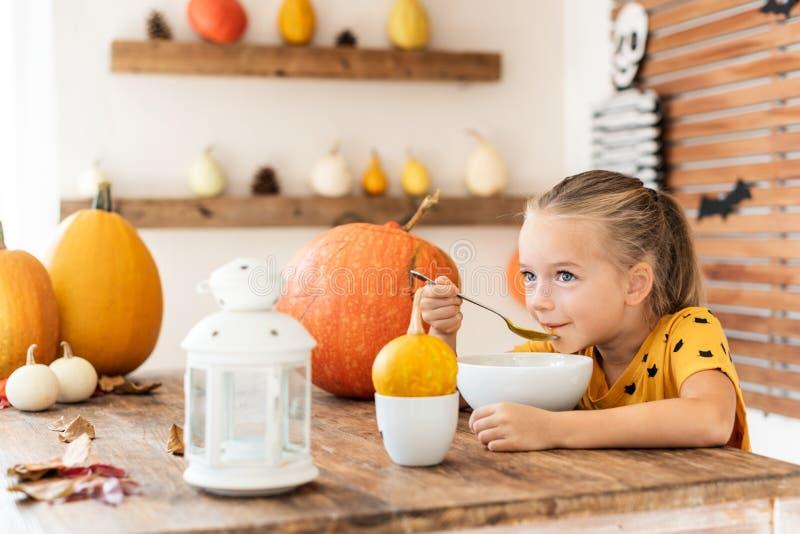 La niña linda que comía la sopa de la calabaza en Halloween adornó el sitio dinning Comida de la comodidad de la estación del oto foto de archivo libre de regalías