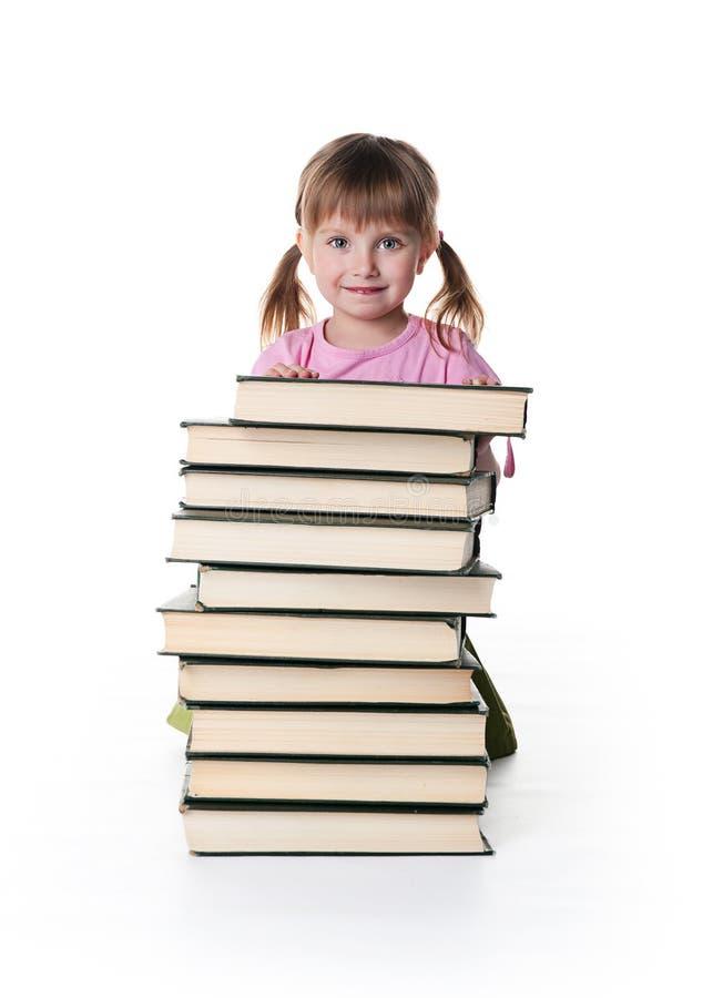 La niña linda se sienta cerca de una pila de libros grandes fotos de archivo