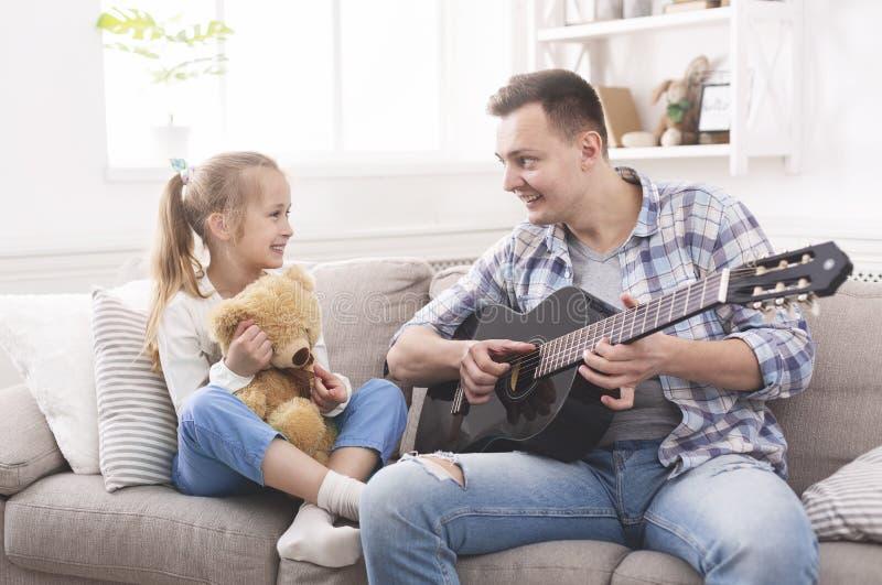 La niña linda y su padre hermoso están tocando la guitarra fotos de archivo libres de regalías