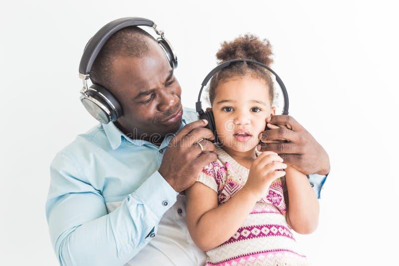 La niña linda y su papá están escuchando la música con los auriculares en un fondo blanco imagen de archivo