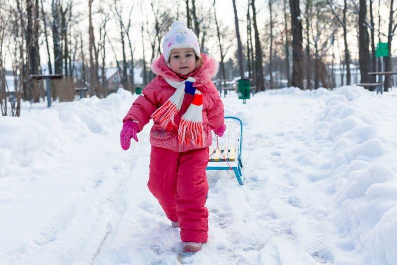 La niña lleva su trineo imagen de archivo libre de regalías