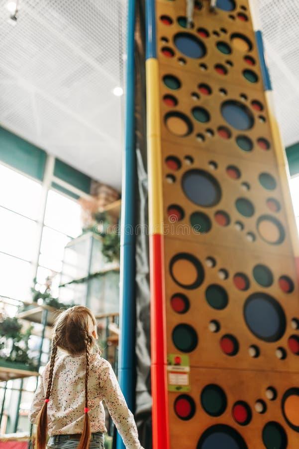 La niña mira en la pared que sube, centro de juego imagenes de archivo