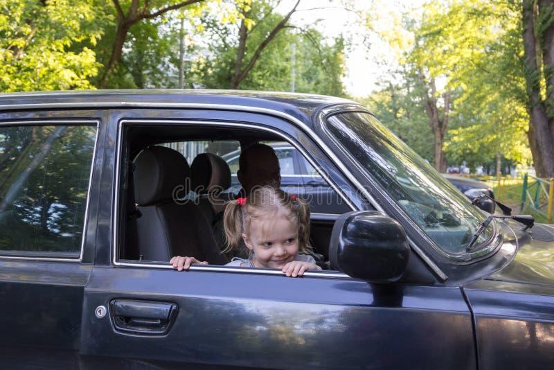 La niña mira fuera del coche de abuelo fotografía de archivo
