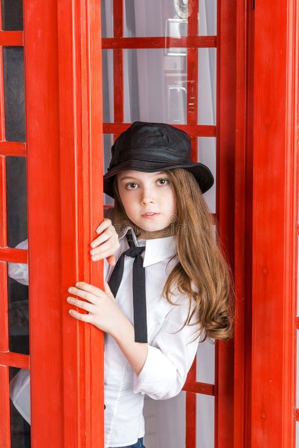 La niña mira hacia fuera de una cabina de teléfono fotografía de archivo libre de regalías