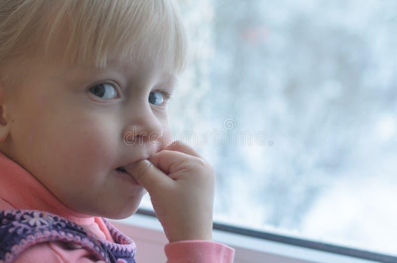 La niña mira hacia fuera la ventana foto de archivo libre de regalías