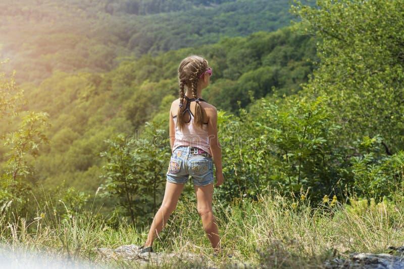La niña mira las montañas del alto Una muchacha coloca una colina en un día soleado del verano imagen de archivo