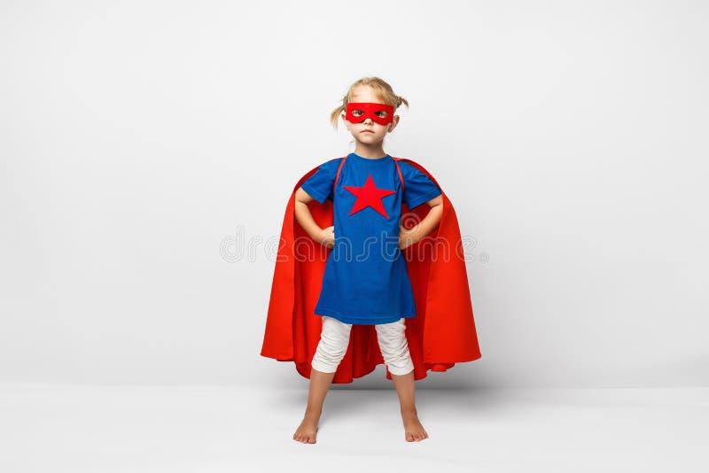La niña muy emocionada se vistió como el super héroe que saltaba junto a la pared blanca foto de archivo