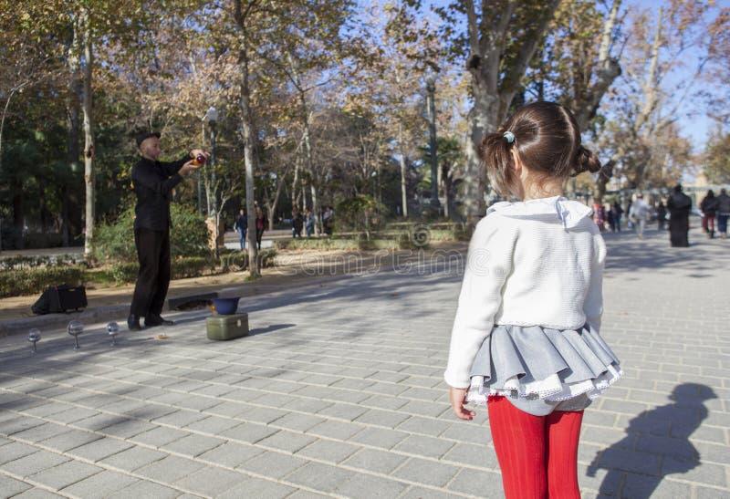 La niña observa a un juglar con demostraciones de las bolas de cristal imagen de archivo